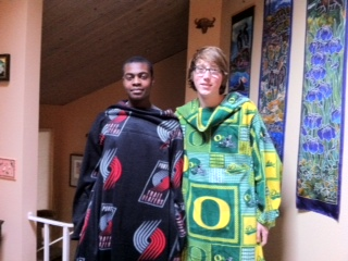 two teens in wearable blankets Trailblazers and UO logos