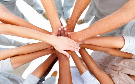 many hands together in circle