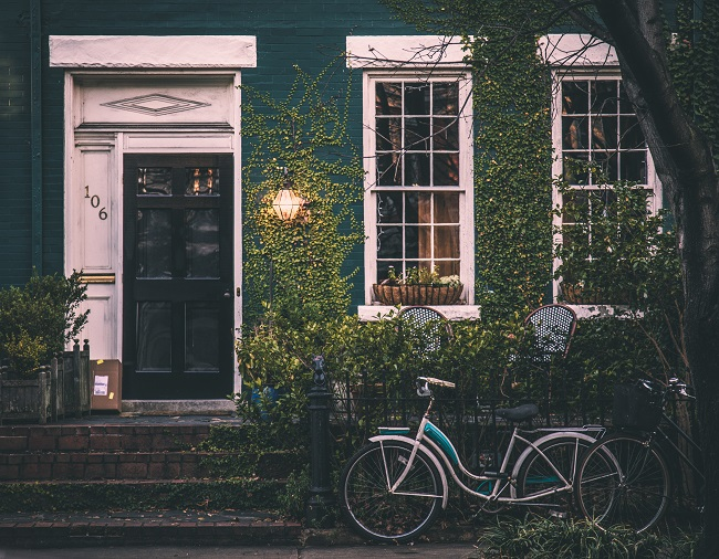 ivy covered home with bicycle in front