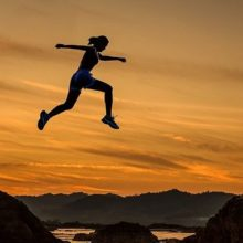 Woman leaping over chasm at dusk