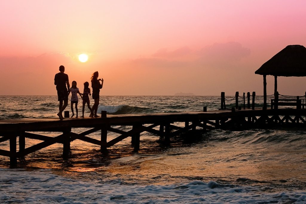 family at sunrise on pier