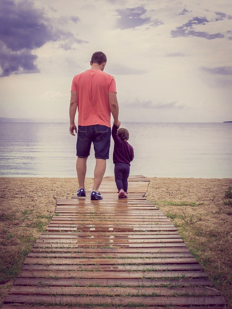 father and son walking towards beach