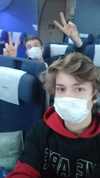 two students with virus masks on airplane