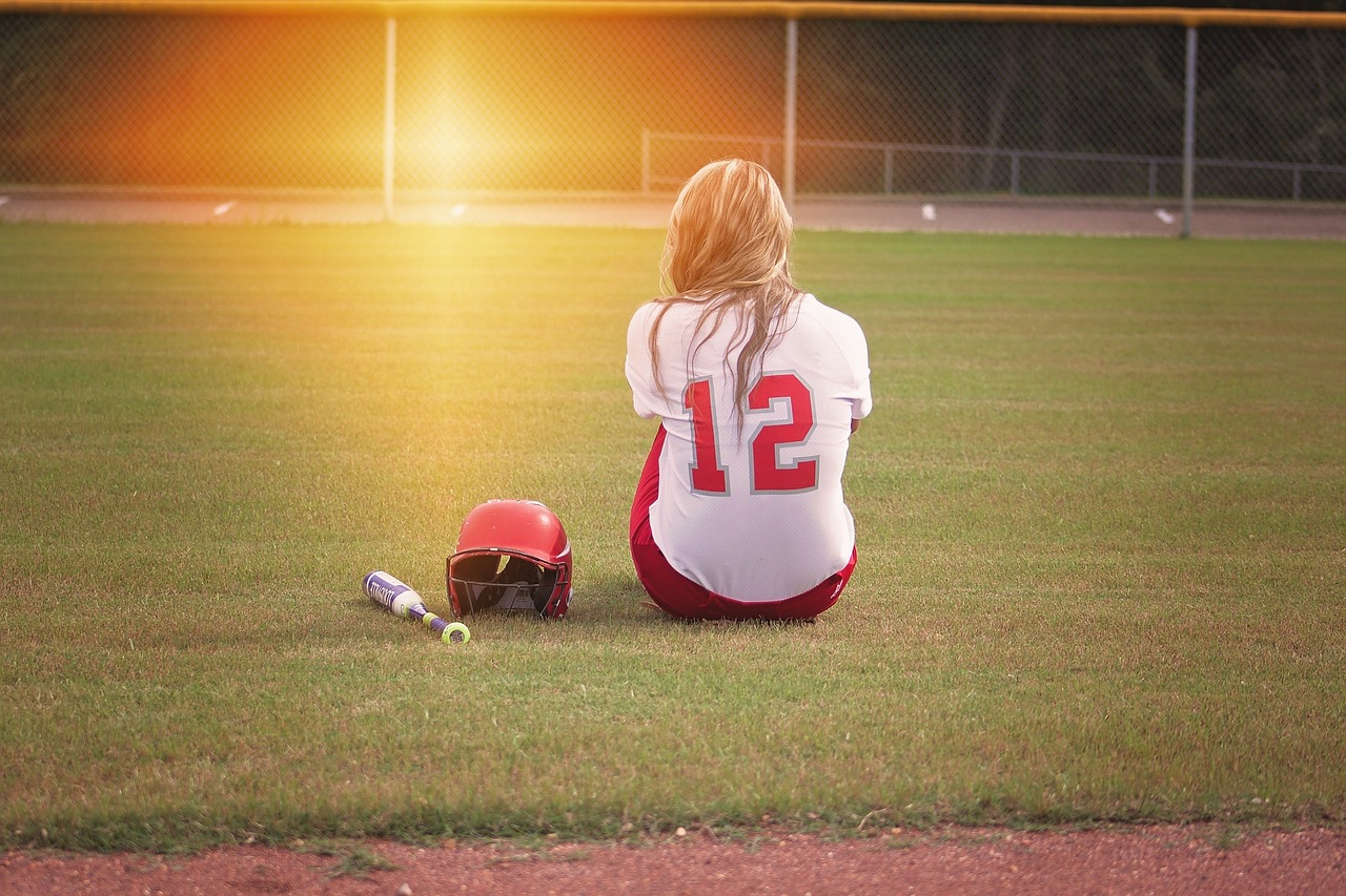 girl in softball uniform alone on field